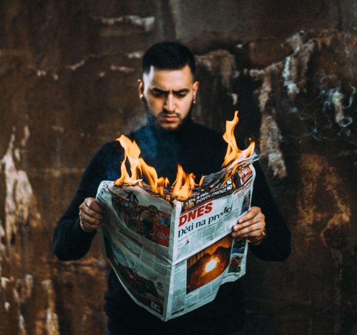 Ragazzo che tiene in mano un giornale in fiamme - Miti sul disturbo bipolare
